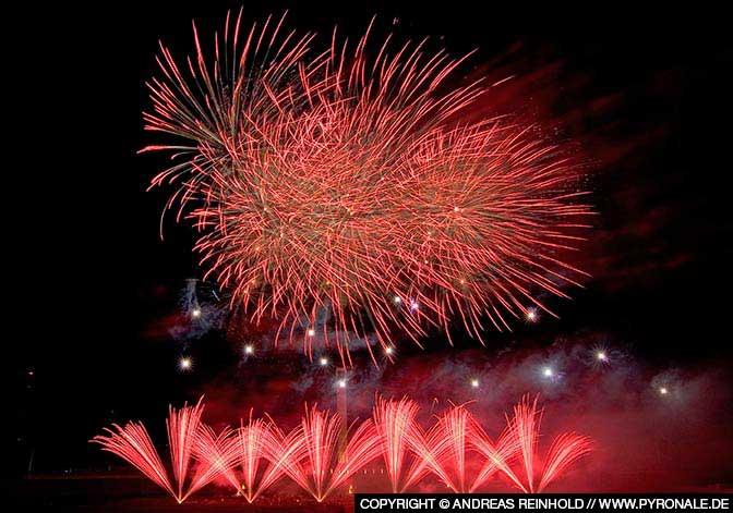 Feuerwerk ganz in Rot - Päonien am Himmel und Feuertöpfe am Boden.