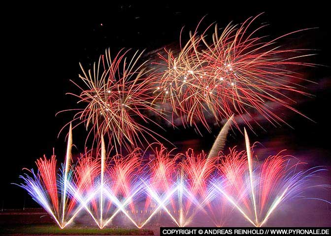 Feuerwerk mit roten Päonien und blau-roten Bodeneffekten.